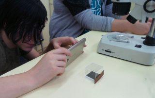 Alumno haciendo una foto a un mosquito tigre con su móvil y lupas binoculares.